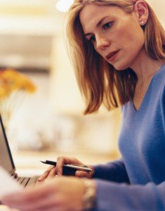 woman reviewing paperwork while on laptop