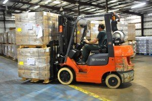 employee moving allets of boxes in warehouse with forklift